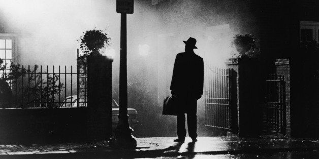 A silhouette of a man stands in front of a house at night in a still from the film,' The Exorcist', directed by William Fried
