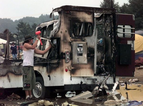 After the riots subside, a concertgoer hammers at a pay phone in a tarnished phone truck.