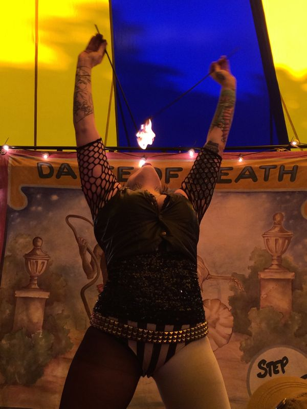 "Tess LaCoil, the ""Pain Proof Pinup"" of the Hellzapoppin circus sideshow group, takes a taste of flame during a mid-day perfor"