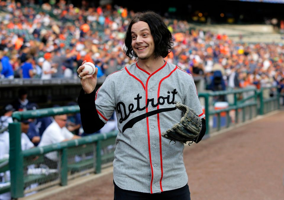 Musician Jack White shows off a baseball before throwing out the ceremonial first pitch before the Detroit Tigers baseball ga