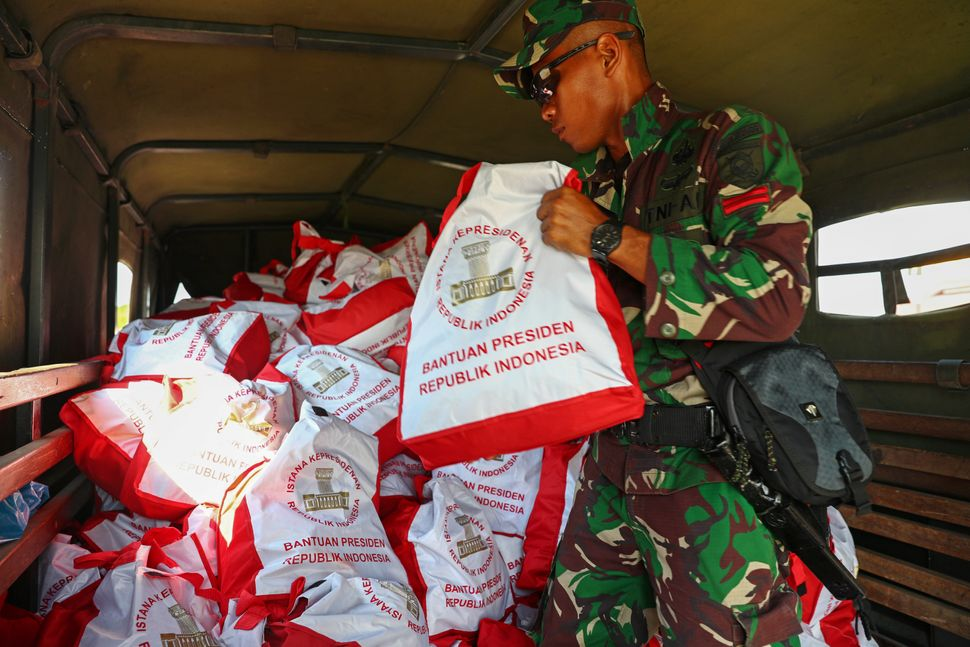 Soldiers unload relief supplies from a military aircraft at Mutiara Sis Al Jufri Airport in Palu.