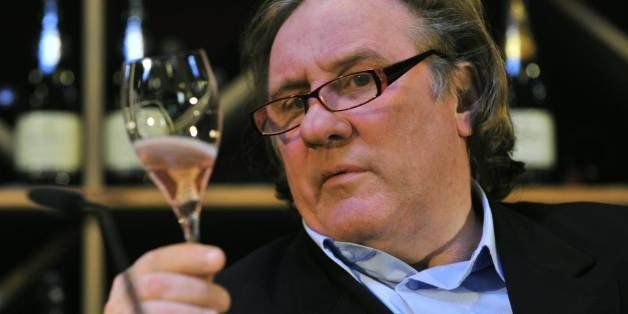 French actor Gerard Depardieu holds up a sample of his sparkling rose wine during a wine presentation in a Berlin wine shop N