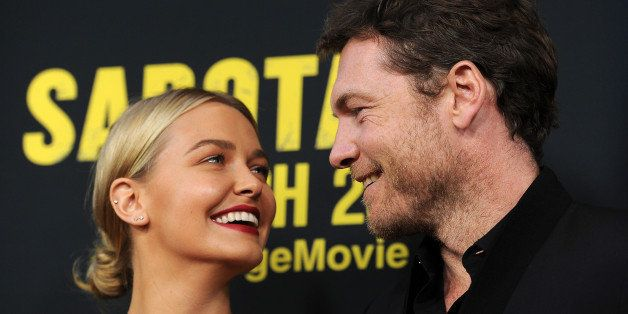 "Sam Worthington, a cast member in ""Sabotage,"" poses with his girlfriend Lara Bingle at the premiere of the film on Wednesday,"