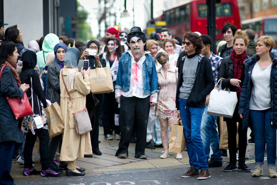 People dressed as zombies parade along Oxford Street, London, as part of World Zombie Day.