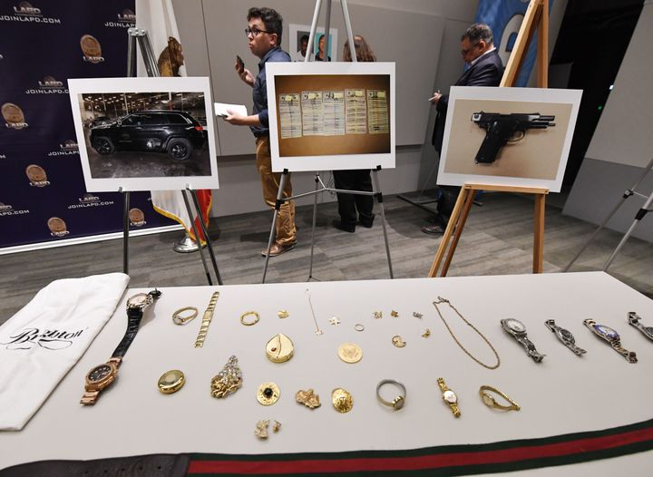 Police displayed seized items believed to have been stolen — including expensive purses, handbags, watches and jewelry