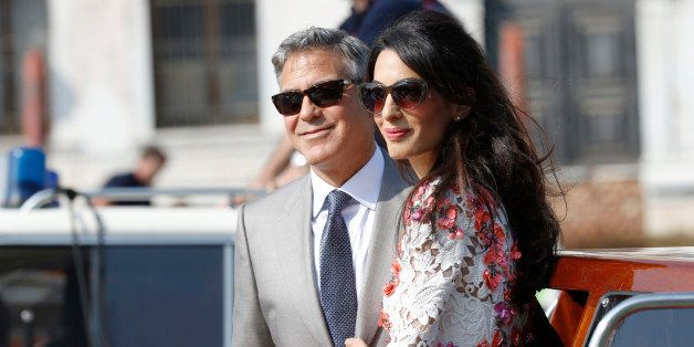 George Clooney is flanked by his wife Amal Alamuddin as they leave the Aman luxury Hotel in Venice, Italy, Sunday, Sept. 28,