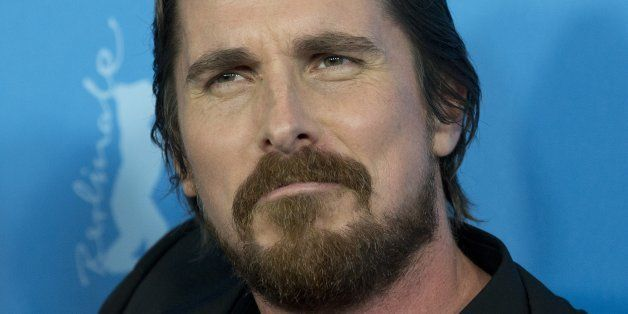Actor Christian Bale jokingly grimaces at photographers during the photo call for the film American Hustle during the Interna
