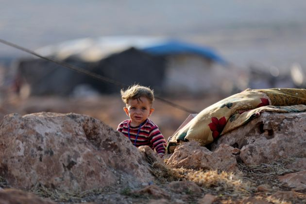 A newly displaced Syrian child walks near a refugee