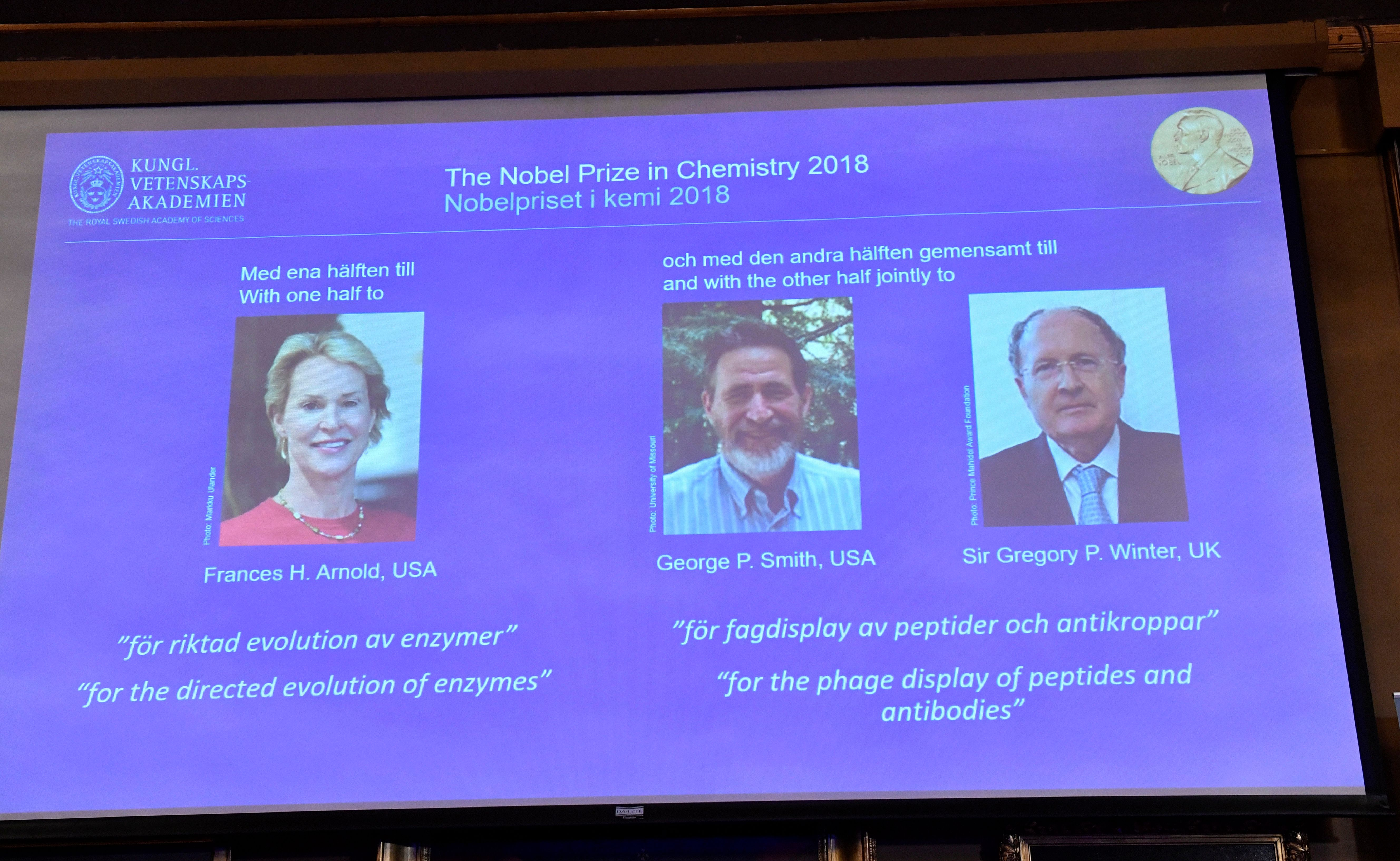 The 2018 Nobel Prize laureates for chemistry are shown on the screen from left, Frances H. Arnold of the U.S., George P. Smit