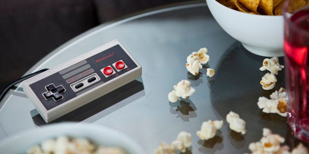 A vintage Nintendo NES controller photographed on a glass table, surrounded by bowls of snacks, taken on July 9, 2013. (Photo