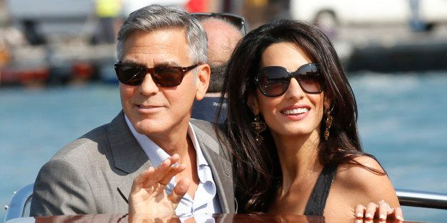 George Clooney, left, and Amal Alamuddin arrive in Venice, Italy, Friday, Sept. 26, 2014. Clooney, 53, and Alamuddin, 36, are