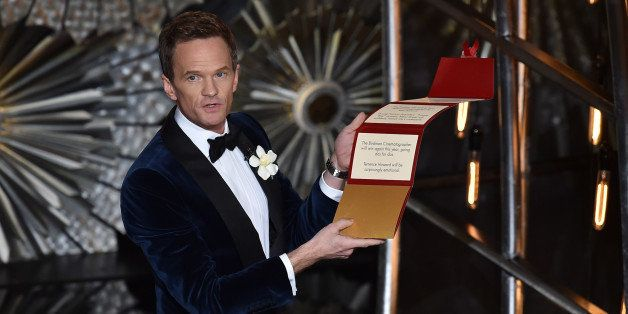 HOLLYWOOD, CA - FEBRUARY 22:  Host Neil Patrick Harris opens his locked envelope onstage during the 87th Annual Academy Award