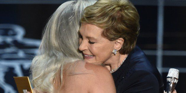 Julie Andrews (R) hugs Lady Gaga on stage at the 87th Oscars February 22, 2015 in Hollywood, California. AFP PHOTO / Robyn BE