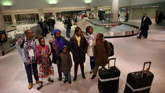 MANCHESTER, NH - FEBRUARY 3: Sendegeya Bayavuge and his family wait for their ride at the ManchesterBoston Regional Airport in Manchester, NH on Feb. 3, 2017. The family of seven from the Democratic Republic of the Congo were greeted by members of the International Institute of New England - Lowell before being escorted to their new home. They are one of the last refugee families to be resettled in New England following President Trumps executive order last week that barred any new refugees for 120 days.  (Photo by Craig F. Walker/The Boston Globe via Getty Images)