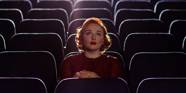 A beautiful young woman with red hair sits alone in a cinema.