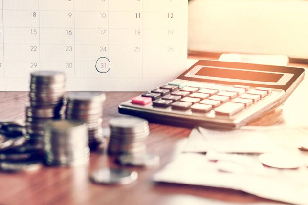 debt collection and tax season concept with deadline calendar remind note,coins,banks,calculator on table,...