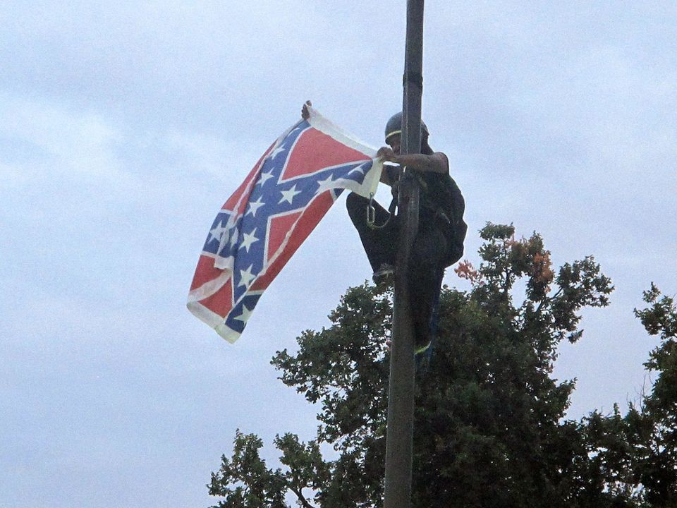 Bree Newsome of Charlotte, N.C., removes the Confederate battle flag at a Confederate monument at the Statehouse in Columbia,