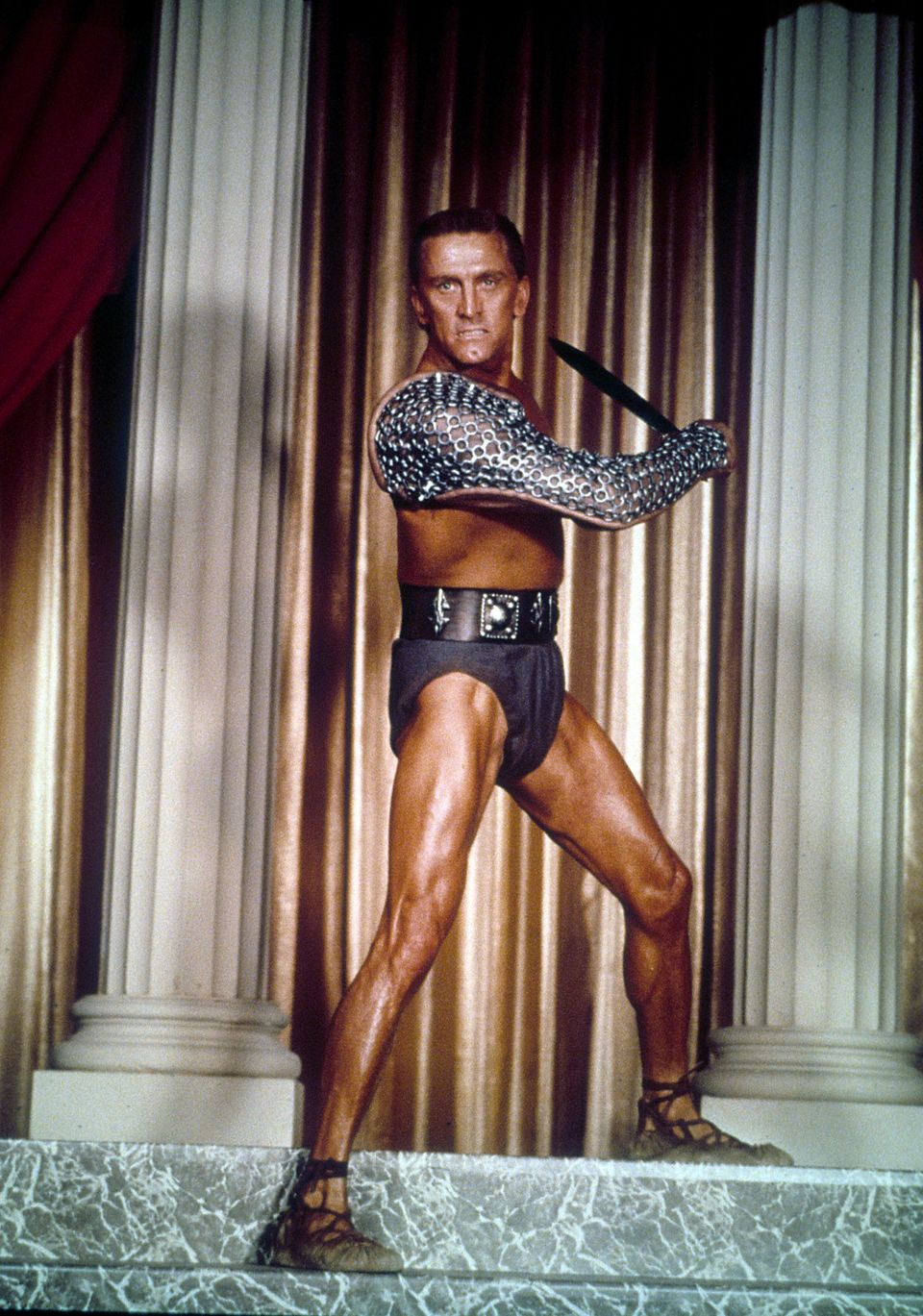 Kirk Douglas the slave Spartacus, standing in between columns holding a sword in a scene from the film 'Spartacus', 1960. (Ph
