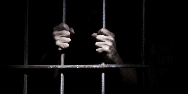 Hands of the prisoner on a steel lattice close up