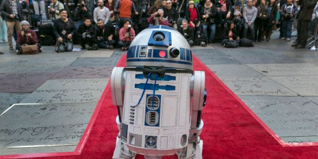 Members of the media are seen as Star Wars' movie character R2-D2 wearing a black bow tie glides down the red carpet for the
