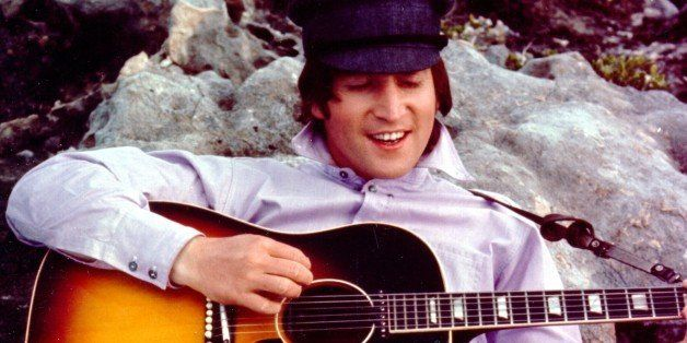 CIRCA 1964: Guitarist John Lennon of the rock and roll band 'The Beatles' poses for a portrait while strumming a Gibson acous