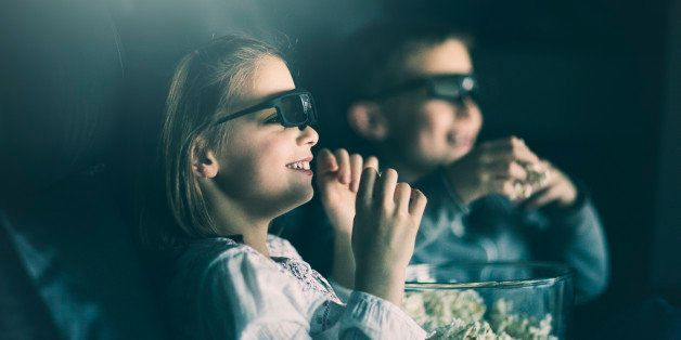 boy and girl wearing 3D glasses watching movie in home theater