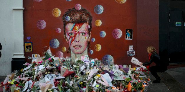 A woman lays flowers beside a mural of British singer David Bowie by artist Jimmy C in Brixton, south London, Tuesday, Jan. 1