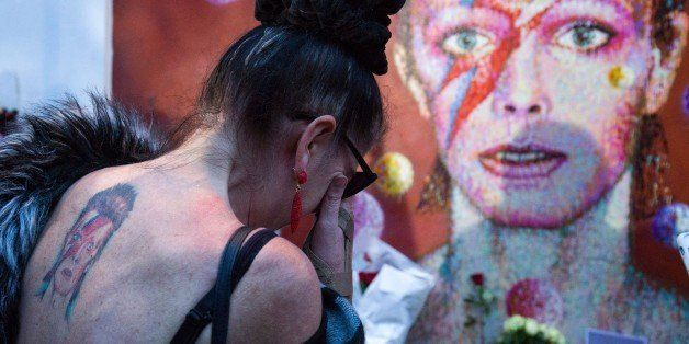 A woman with a tatoo of David Bowie reacts as she pays her respects in front of the British singer, painted by Australian str