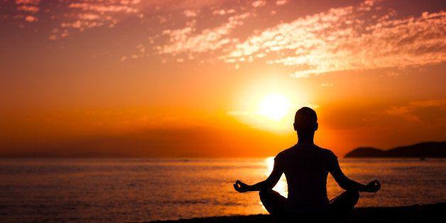 woman doing yoga at sunset
