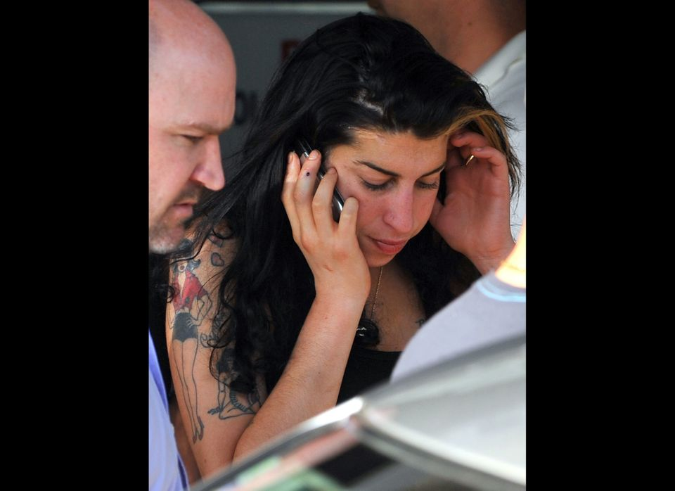 British singer Amy Winehouse uses her mobile phone as she arrives at Belgrade airport June 18, 2011. AFP PHOTO / ANDREJ ISAKO