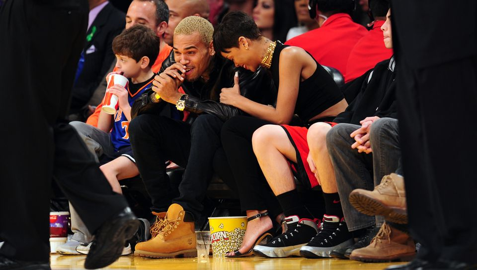 Rihanna (R) and Chris Brown (L) attend an NBA game between the New York Knicks and the Los Angeles Lakers at Staples Center i