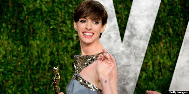 Anne Hathaway carrying her Oscar for best supporting actress arrives for the 2013 Vanity Fair Oscar Party on February 24, 201