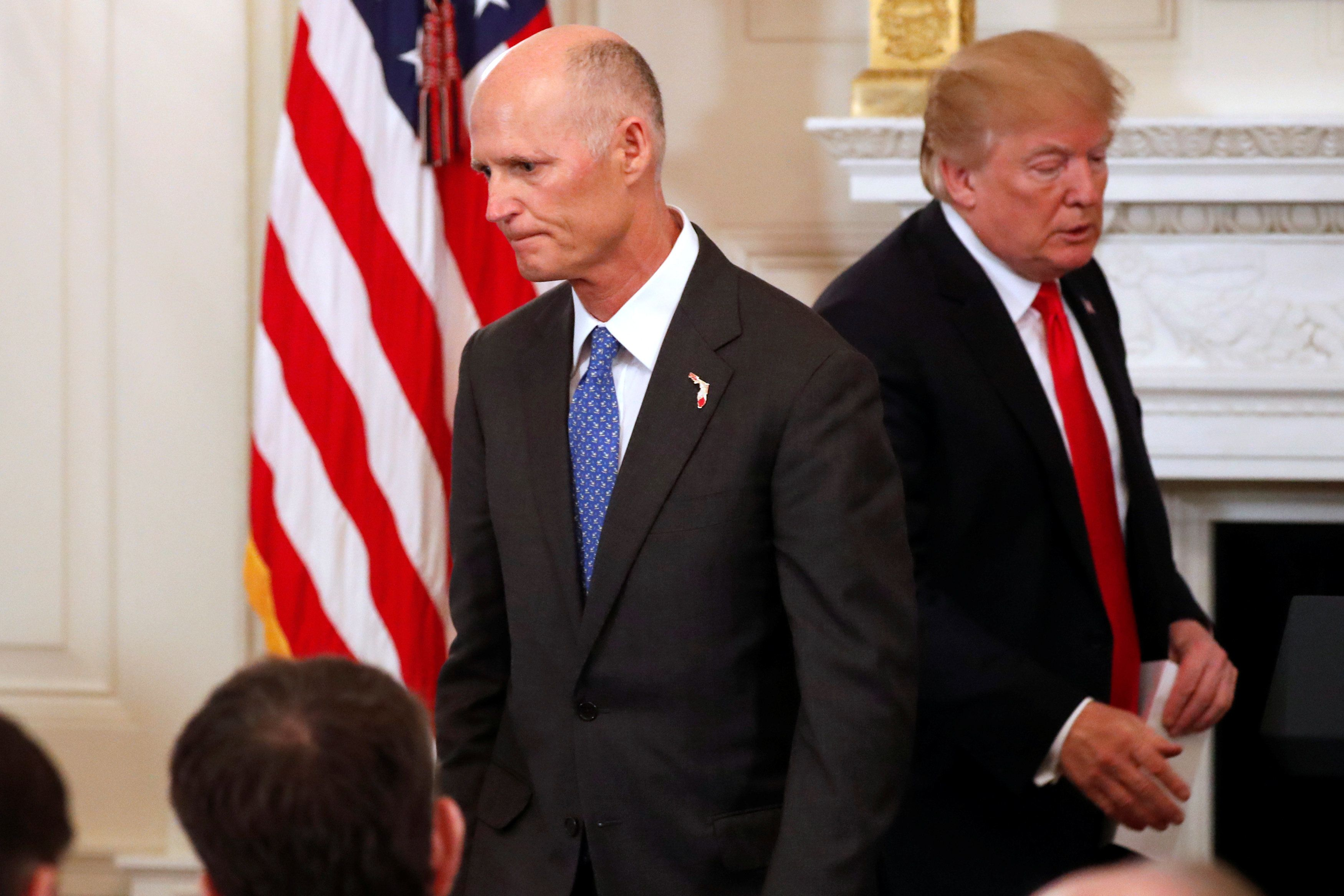 Florida Governor Rick Scott and U.S. President Donald Trump cross paths during a discussion about school shootings with state governors from around the country at the White House in Washington, U.S. February 26, 2018.  REUTERS/Jonathan Ernst