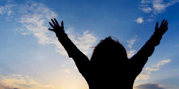 woman silhouette with arms raised praying.