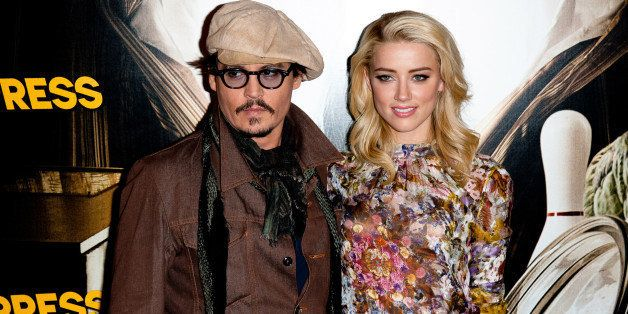 PARIS, FRANCE - NOVEMBER 08:  Johnny Depp and Amber Heard pose during the 'Rhum Express' Photocall at Hotel Paris Plaza Athen