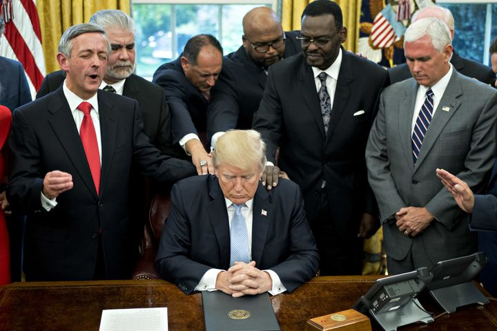 President Donald Trump bows his head as faith leaders and evangelical ministers pray over him after he signed a proclamation