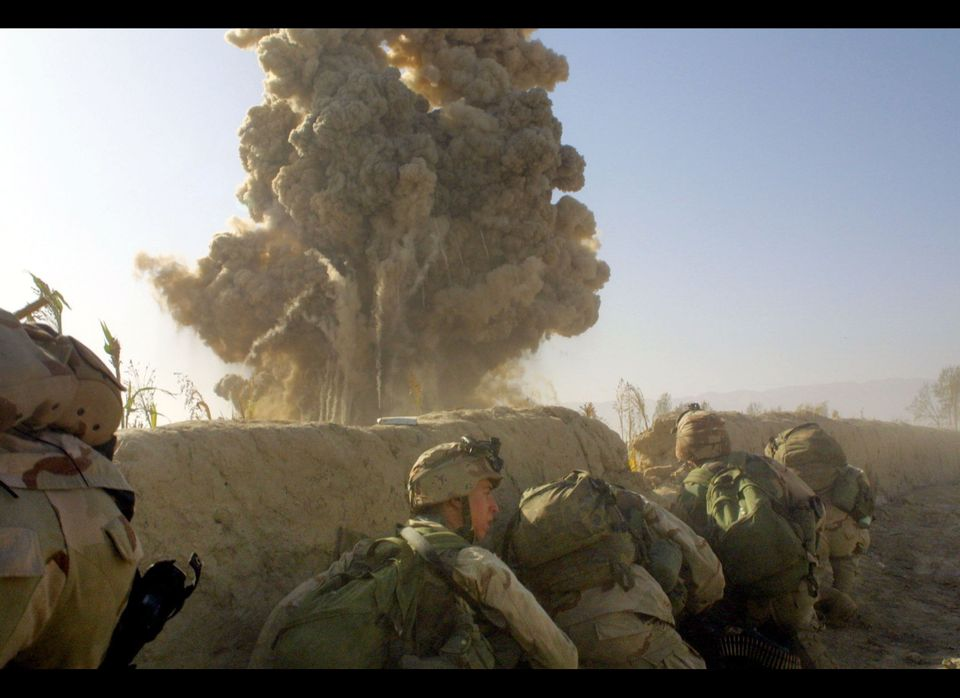 <em>American soldiers hide behind a barricade during an explosion, prior to fighting with Taliban forces November 26, 2001 at