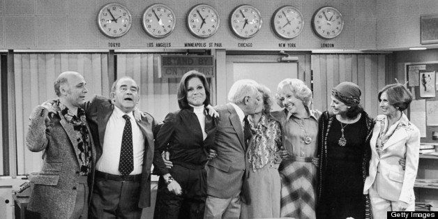 1977:  The cast of 'The Mary Tyler Moore Show' stands with their arms around each other in the newsroom in a promotional port