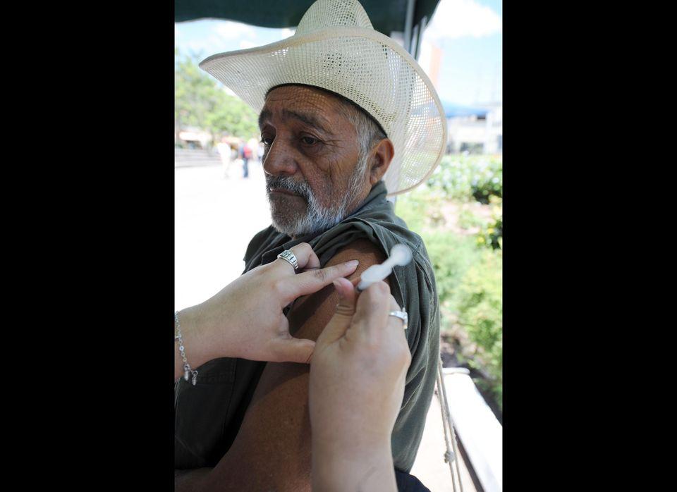 A senior citizen is vaccinated against tetanus and Influenza A H1N1 in Tegucigalpa March 24, 2010. AFP PHOTO/Orlando SIERRA.