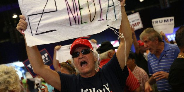 WEST PALM BEACH, FL - OCTOBER 13: A man holds a sign towards the media as he attends a campaign rally for Republican presiden