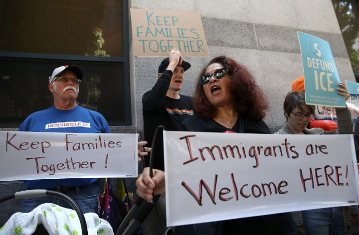 Protesters hold signs during a demonstration outside of the San Francisco office of the Immigration and Cutsoms Enforcement i
