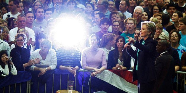 Democratic presidential candidate US Senator Hillary Clinton (D-NY) is lit by the flash from an audience member's camera at a