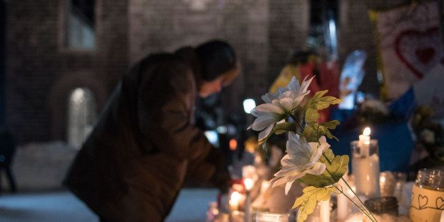 People place candles near a mosque that was the location of a shooting spree in Quebec City, Quebec on January 31, 2017. Ale