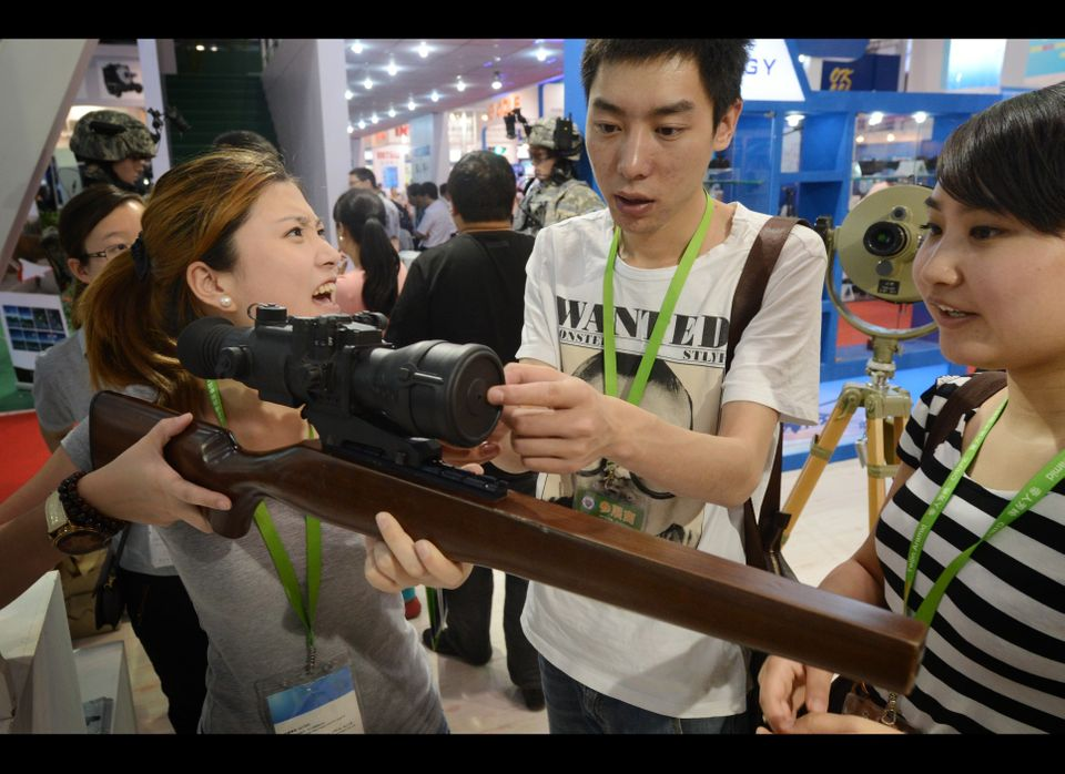 A couple try out thermal rifle sights on display at the Asia Pacific China Police exhibition in Beijing on May 24, 2012. The
