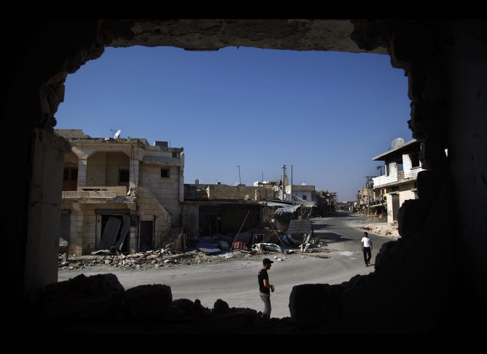 In this Sunday Aug. 5, 2012 photo, Syrians are seen through a destroyed wall as they walk on a street in town of Atareb outsk