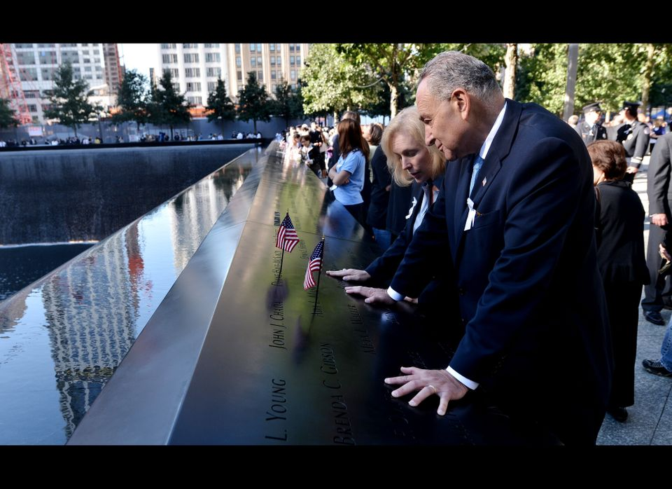 U.S Senators Kirsten Gillibrand, and Charles Schumer, D-NY, place American flags in names engraved in the border of one of th