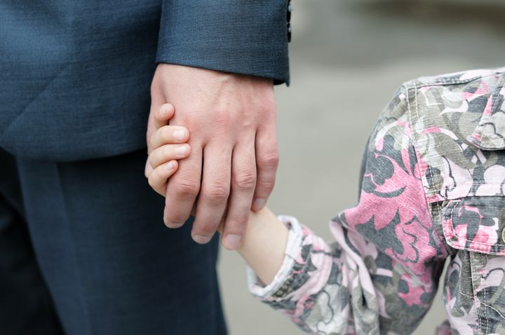 Closeup of a small girl holding a man's hand