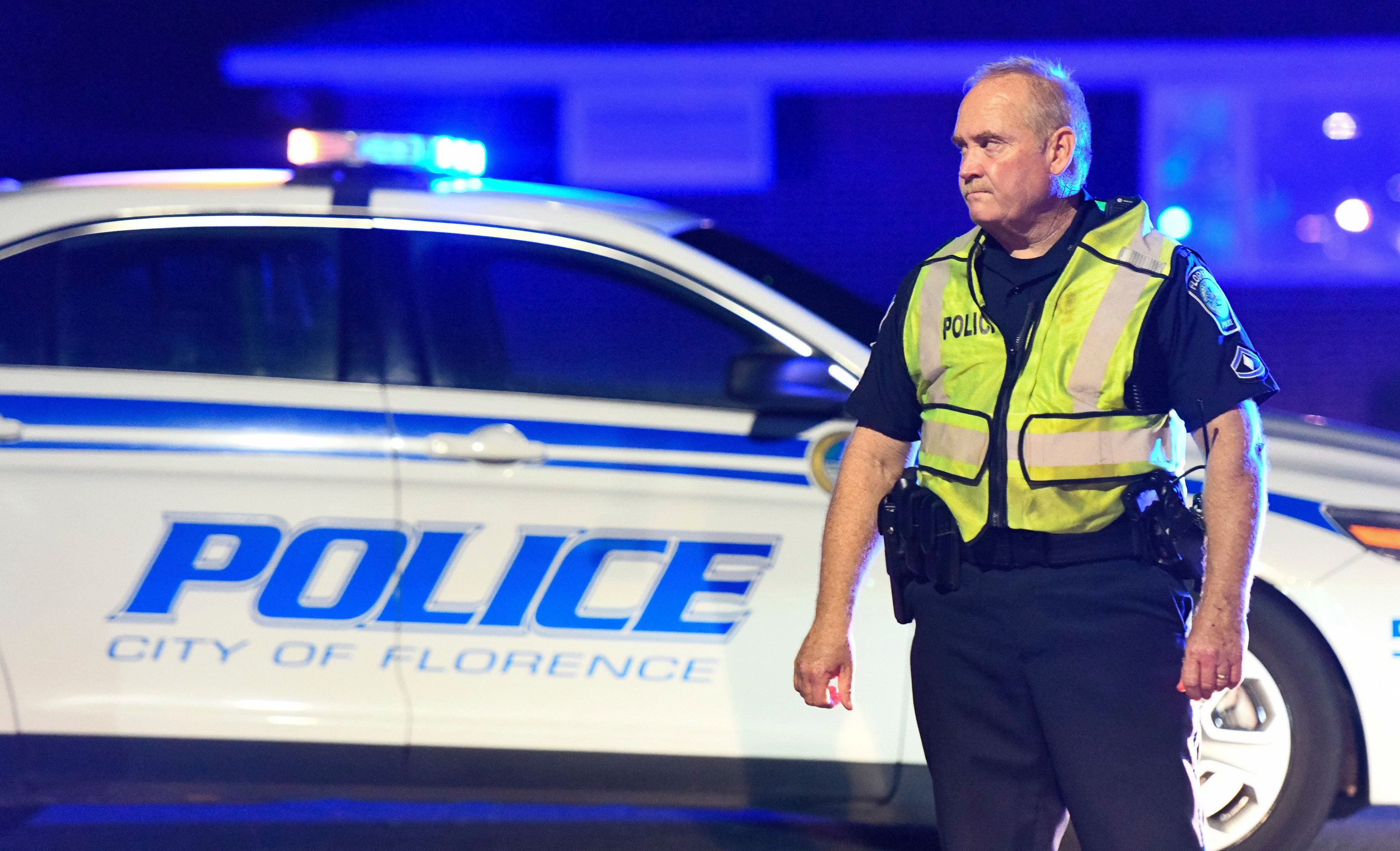 A police officer directs traffic on Hoffmeyer Road near the Vintage Place neighborhood where three deputies and two city officers were shot Wednesday in Florence SC AP Photo/Sean Rayford