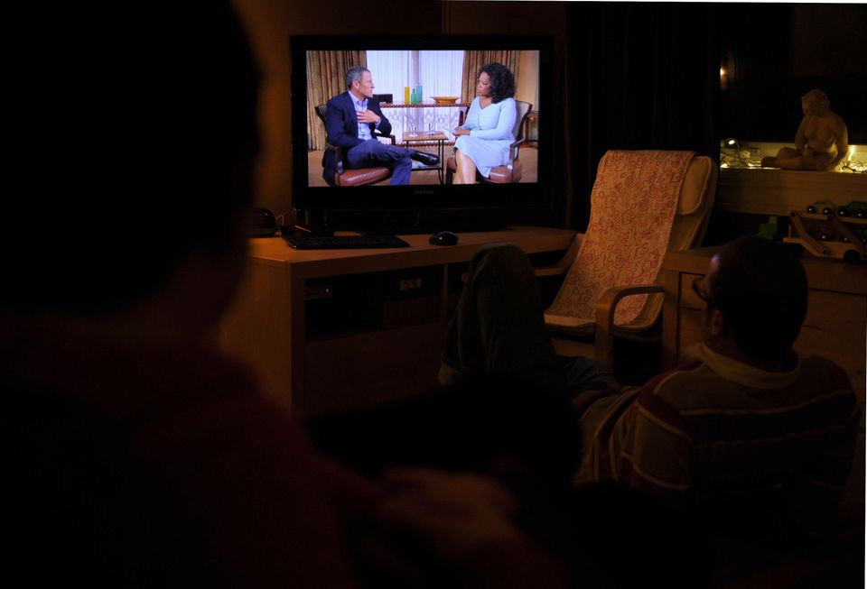 A photo illustration shows people watching a TV showing disgraced cycling star Lance Armstrong (L) being interviewed by Oprah