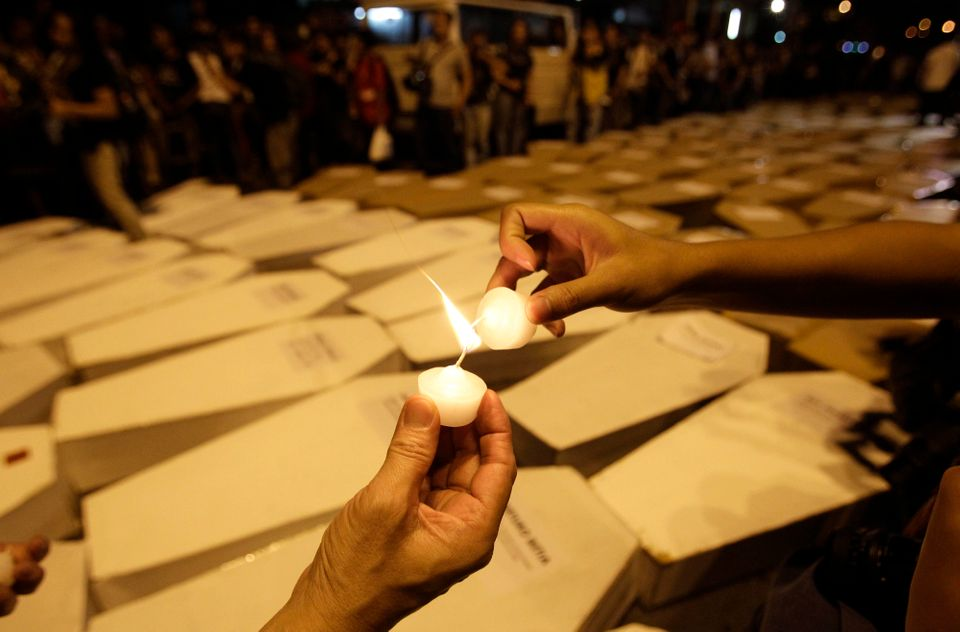 Filipino journalists and supporters light candles to be placed on top of mock coffins during a rally to denounce killings of